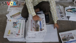 FILE - A Bangladeshi worker sorts newspapers, in Dhaka, Bangladesh, Feb. 20, 2016. Under Section 57 of Bangladesh's Information and Communications Technology Act, journalists can be jailed for offenses such as defamation or hurting religious sentiment.