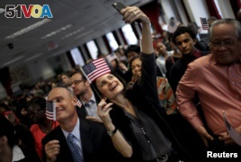 A new U.S. citizen takes a selfie after taking the Oath of Allegiance during a special naturalization ceremony at the U.S. Citizenship and Immigration Services District Office in New York City, Nov. 13, 2015. REUTERS/Mike Segar