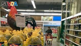 A shopper pushes a cart down a quiet Lotte Mart in Beijing, China, March 17, 2017. (AP)