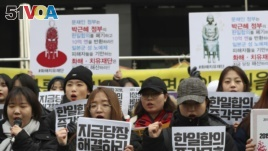 South Korean students shout slogans during a press conference about the 2015 agreement between South Korea and Japan near the Japanese Embassy in Seoul, South Korea, Thursday, Dec. 28, 2017.