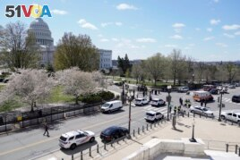 Police officers surround the scene after a car that crashed into a barrier on Capitol Hill on the Senate side of the U.S. Capitol in Washington, Friday, April 2, 2021. (AP Photo/J. Scott Applewhite)