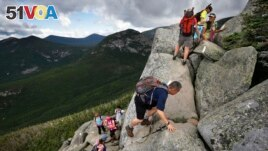 In this Saturday, Aug. 7, 2015 photo, day-hikers scramble over rocky boulders on the Appalachian Trail below the summit of Mt. Katahdin in Baxter State Park in Maine. (AP Photo/Robert F. Bukaty)