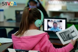 Students at Driggers Elementary School attend a class in-person as they interact with classmates virtually, Monday, Feb. 8, 2021, in San Antonio. (AP Photo/Eric Gay)