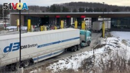 FILE - In this Wednesday, March 18, 2020 file photo, truck traffic from Canada waits to cross the border into the United States in Derby Line Vt. The U.S. will reopen its land borders to nonessential travel next month. (AP Photo/Wilson Ring, File)