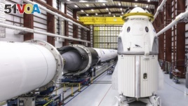 In this Dec. 18, 2018 photo provided by SpaceX, SpaceX's Crew Dragon spacecraft and Falcon 9 rocket are positioned inside the company's hangar at Launch Complex 39A at NASA's Kennedy Space Center in Florida. (Space X via AP)