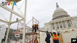 Construction continues on the Inaugural platform in preparation for the Inauguration and swearing-in ceremonies for President-elect Donald Trump on the Capitol steps in Washington. Trump will be sworn in a president on Jan. 20, 2017. (AP Photo/Pablo Martinez Monsivais)