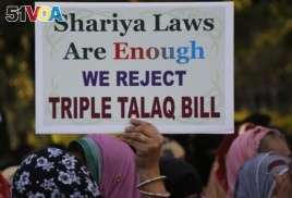 In this Jan. 7, 2018 file photo, an Indian Muslim woman holds a placard during a protest against a new draft law aimed at banning