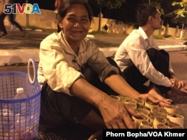 A vendor from Kampong Chhnang province complains that her sticky rice cake business is not good this year due to the cancellation of boat races. Phnom Penh, Cambodia, Thursday, November 26, 2015. (Phorn Bopha/VOA Khmer)