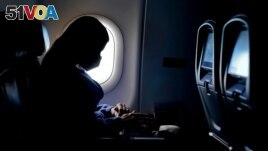 FILE - In this Feb. 3, 2021 file photo, a passenger wears a face mask during an airline flight after taking off from Atlanta.