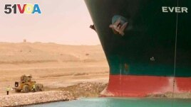 In this photo released by the Suez Canal Authority, a cargo ship, named the Ever Given, sits with its bow stuck into the wall Wednesday, March 24, 2021, after it become wedged across Egypt's Suez Canal and blocked all traffic in the vital waterway.