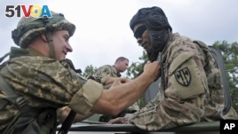 US and Ukrainian servicemen talk during the opening ceremony for the Rapid Trident/Saber Guardian 2015 military exercises in Ukraine,  July 20, 2015. (AP Photo/Pavlo Palamarchuk)