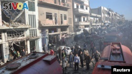 Syrian army soldiers and civilians inspect the site of two bombings in the Syrian city of Homs, in this photo provided by the state-owned Syrian Arab News Agency (SANA), Dec. 28, 2015.
