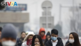 A woman uses a scarf and others wear masks to cover their face from pollutants as they walk along a street on a polluted day in Beijing, Tuesday, Dec. 8, 2015.