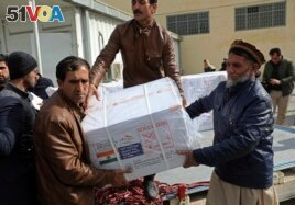 Afghan health ministry workers unloads boxes of the first shipment of 500,000 doses of the AstraZeneca coronavirus vaccine made by Serum Institute of India, donated by the Indian government to Afghanistan.