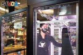 Vanesa Peredo, owner of A Taste of Spain, serves customers at Reading Terminal Market that has seen reduced foot traffic due to the coronavirus disease (COVID-19) outbreak in Philadelphia, Pennsylvania, U.S., February 20, 2021. (REUTERS/Hannah Beier)