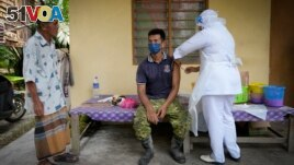 A nurse administers a Pfizer COVID-19 vaccine to a farmer outside his home in rural Sabab Bernam, central Selangor state, Malaysia, Tuesday, July 13, 2021. (AP Photo/Vincent Thian)
