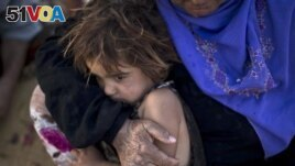 In this Aug. 23, 2015 file photo, elderly Syrian refugee Halima Ali holds her granddaughter Amal, 4, while sitting outside their tent at an informal tented settlement near the Syrian border on the outskirts of Mafraq, Jordan. In 2015, there were over 65 million displaced people, the most since World War II, according to the United Nations. Continued conflicts and persecution in places like Syria and Afghanistan fueled the increase. (AP Photo/Muhammed Muheisen)