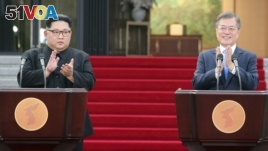 FILE - North Korean leader Kim Jong Un, left, and South Korean President Moon Jae-in applaud after their joint announcement at the border village of Panmunjom in the Demilitarized Zone, South Korea, Friday, April 27, 2018. The two will meet again on Sept. 18 in the North's capital. (Korea Summit Press Pool via AP)