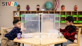 Preschool students eat lunch at Dawes Elementary in Chicago. Pressure is building on school systems around the U.S. to reopen classrooms to students who have been learning online for nearly a year.(Ashlee Rezin Garcia/Chicago Sun-Times via AP, Pool, File)