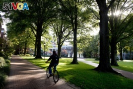 A student rides a bicycle across campus at Elon University in Elon, North Carolina.