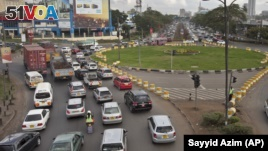 Drivers sit at a traffic circle with its exits blocked off by barriers to prevent right turns, on a highway in downtown Nairobi, Kenya Tuesday, April 14, 2015. (AP Photo/Sayyid Azim)