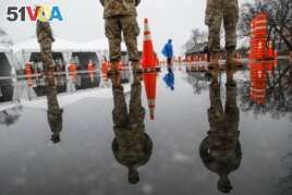 National Guard personnel stand at attention as they wait for patients to arrive for COVID-19 coronavirus testing facility at Glen Island Park, in New Rochelle, N.Y.