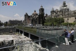 People observe the archaeological site of Templo Mayor in the historic center of Mexico City, Tuesday, May 18, 2021.(AP Photo/Eduardo Verdugo)