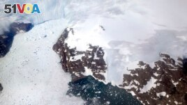 FILE - In this file photo dated Thursday, Aug. 3, 2017, a glacier at left calves icebergs into a fjord off the Greenland ice sheet in southeastern Greenland. (AP Photo/David Goldman, FILE)