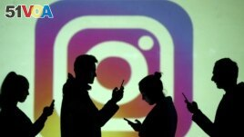 In this file photo, silhouettes of mobile users are seen next to a screen projection of the Instagram logo in this picture illustration taken March 28, 2018. (REUTERS/Dado Ruvic/Illustration/File Photo)