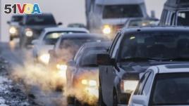 FILE - Car exhaust billows around commuter traffic in winter weather in Omaha, Nebraska, Feb. 1, 2013.