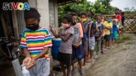 Aeta students queue to sanitize their hands before a session at the makeshift rickshaw learning center for Aeta community distance learning amid the COVID-19 pandemic, in Porac, Pampanga, Philippines, October 12, 2020.