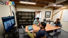 RunX CEO Ankur Dahiya, center, takes part in a video meeting with employees JD Palomino, top left, and Nitin Aggarwal, right, at a temporary office in San Francisco, Friday, Aug. 27, 2021. Technology companies like RunX that led the move into remote work early as the pandemic started, are facing a new difficulty as it calms down: how, when and even if they should bring their employees back to offices that have been made for teamwork. (AP Photo/Eric Risberg)