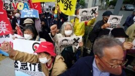 People chant slogans against government's decision to start releasing massive amounts of treated radioactive water from the wrecked Fukushima nuclear plant into the sea, during a rally outside the prime minister's office in Tokyo Tuesday, April 13, 2021.