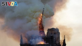 The steeple and spire of the landmark Notre-Dame Cathedral collapses as the cathedral is engulfed in flames in central Paris on April 15, 2019.