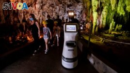 Persephone guides the visitors inside Alistrati cave, about 135 kilometers northeast of Thessaloniki, Greece, Monday, Aug. 2, 2021. (AP Photo/Giannis Papanikos)