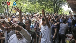 In this June 25, 2018 file photo, a group of protesters chant slogans at the old grand bazaar in Tehran, Iran.