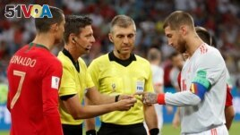 Here, referee Gianluca Rocchi does a pre-match coin toss between Portugal's Cristiano Ronaldo and Spain's Sergio Ramos, June 15, 2018. (REUTERS/Murad Sezer)