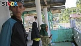 Local young people wait for a Quran reading class to start at a mosque in a village which is feared will be affected by the expansion of the Asia Pulp & Paper, a company part of Indonesian corporation Sinarmas, in West Bangka, Indonesia.