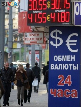 FILE - People walk past an exchange booth in a street in Moscow, Russia, Thursday, Sept. 30, 2010. Russia's Central Bank has ordered to close all exchange booths outside banks starting Oct. 1, 2010. (AP Photo/Mikhail Metzel)