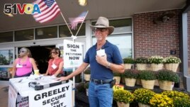 John G. Gauthiere collects signatures outside a grocery store in Greeley, Colorado. (AP Photo/David Zalubowski)
