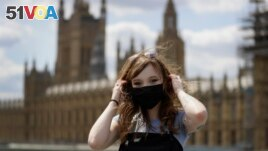 Pictured here, Estelle Fitz poses for a photo as she stands on Westminster Bridge in London, July 22, 2020. But will two masks give us more protection from the virus? (AP Photo/Kirsty Wigglesworth)