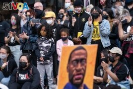 Demonstrators gather for a solidarity rally lead by community organizers in the Black and Asian communities in memory of George Floyd and Daunte Wright outside Cup Foods, Sunday, April 18, 2021, in Minneapolis. (AP Photo/John Minchillo)