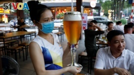 A woman serves beer at a restaurant after the govenment eased nationwide lockdown during the coronavirus disease (COVID-19) outbreak in Hanoi, Vietnam April 29, 2020. (REUTERS/Kham)