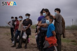 FILE - About a dozen asylum seeking unaccompanied minors from Central America are separated from other migrants by U.S. Border Patrol agents after crossing the Rio Grande river into the United States from Mexico on a raft in Penitas, Texas, U.S., March 14, 2021.