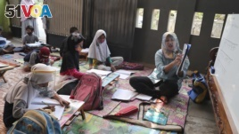 Indonesian teacher Inggit Andini, right, teaches at a makeshift class for students who lack access to the internet to study online, at her residence in Tangerang, Indonesia, on Aug. 10, 2020