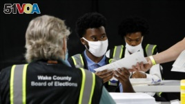 FILE - Poll workers prepare absentee ballots for shipment at the Wake County Board of Elections on the first day that the state started mailing them out, in Raleigh, North Carolina, U.S. September 4, 2020. (REUTERS/Jonathan Drake/File Photo)