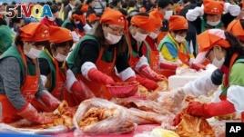 South Koreans and tourists make kimchi to donate to needy neighbors during the Seoul kimchi festival in Seoul, South Korea, Friday, Nov. 6, 2015.