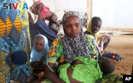 A family of refugees that fled their homes due to violence from the Islamic extremist group Boko Haram sit inside a refugee camp in Minawao, Cameroon, Feb. 25, 2015.