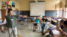 ESL (English-as-a-second-language) teacher Xavier Chavez, standing, teaches a summer history class at Benson High School in Portland, Ore.,Wednesday, Aug. 6, 2008. (AP Photo/Don Ryan)