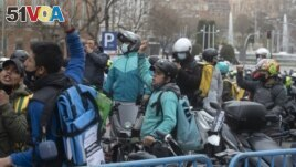 Delivery riders protest outside the Spanish parliament in Madrid, Wednesday March 3, 2021.The Spanish government announced on Thursday March 11, 2021, legislation that classifies food delivery riders as employees of the digital platforms they work for, no